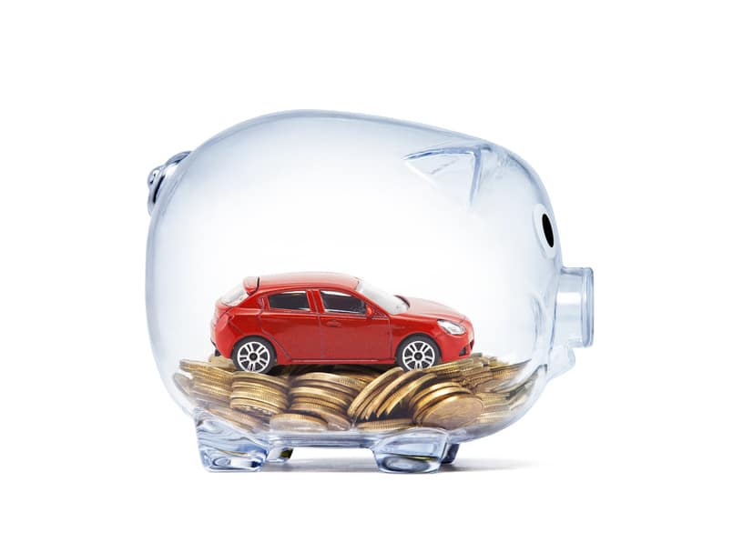 clear piggy bank with red car sitting atop gold coins