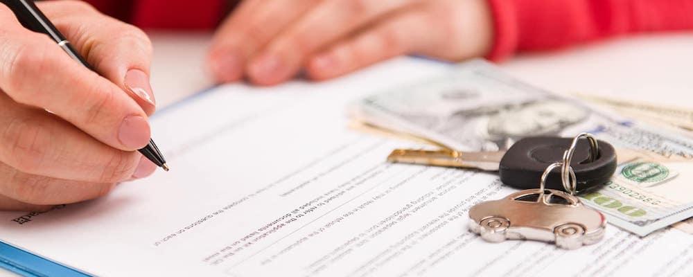 close up of hand signing paperwork next to car keys