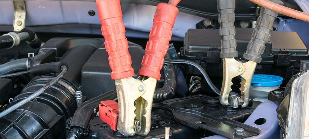 close up of jumper cables attached to car battery