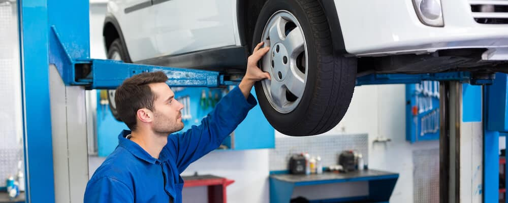mechanic inspecting car tires