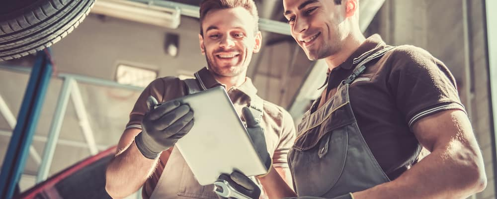 two service technicians looking at checklist while repairing a vehicle