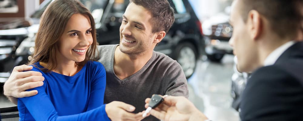 young couple getting keys to car