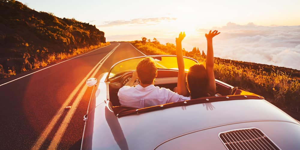 Couple Driving Towards Sunset in Convertible