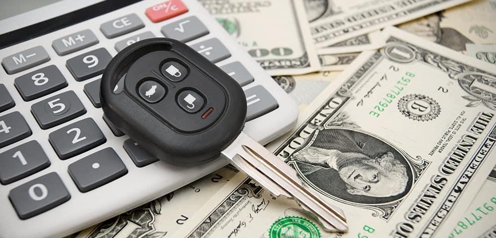 Car key on top of calculator and dollar bills