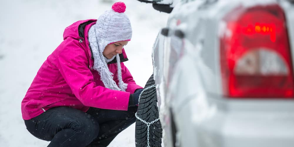 Woman Adjusting Tire Chains on Car