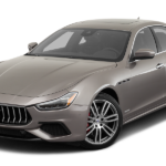 A taupe Maserati Ghibli against a white background.