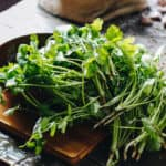 Fresh parsley and cilantro on wooden table