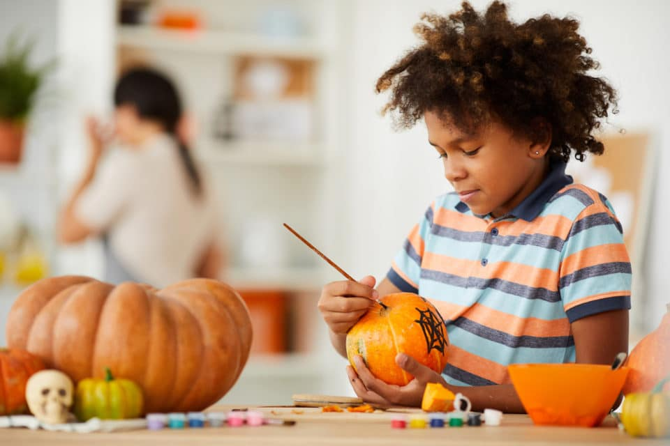 Smiling creative child leaning on counter with gouaches and making design on pumpkin