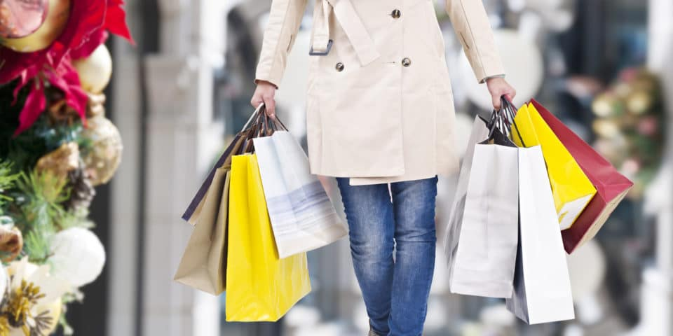A picture of a person from the waist down, who is wearing a light tan trench coat and skinny jeans. They are holding several Christmas shopping bags