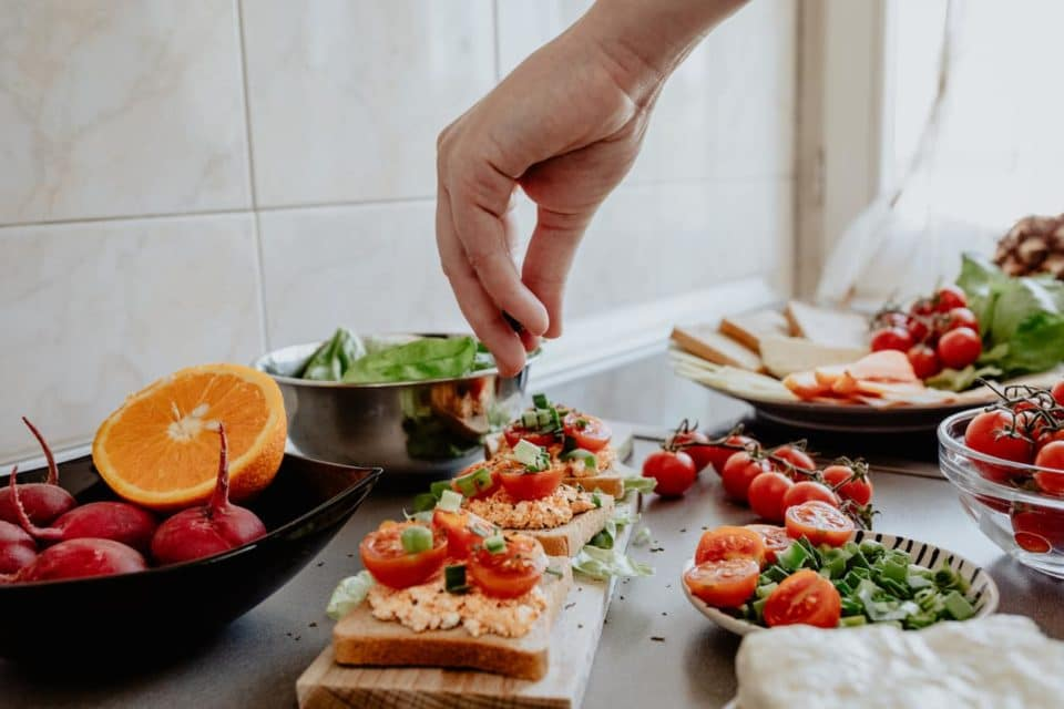 A counter full of vegetables with a vegetarian toast meal on display. A white hand is in the shot to sprinkle salt on the toast.