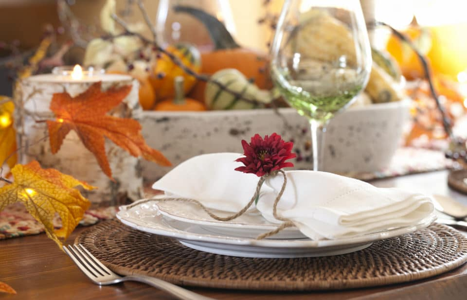 Autumn Thanksgiving holiday dining table place setting with a centerpiece of pumpkins and gourds