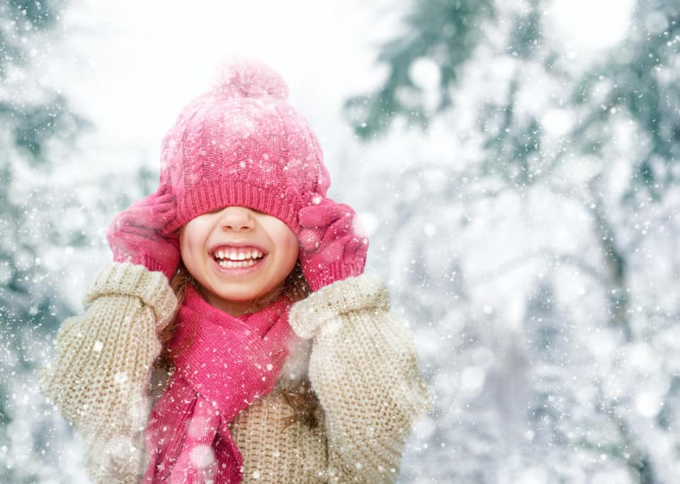 Happy child wearing a tan coat, pink hat, and pink scarf playing on a winter walk in nature