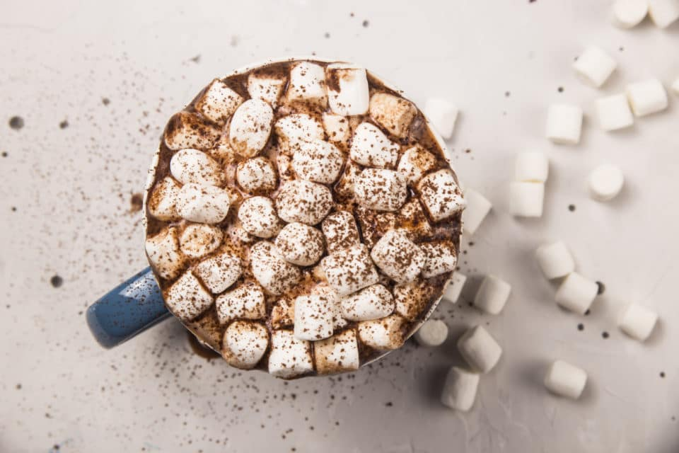 Hot chocolate full of marshmallows in a blue mug. Cocoa powder is sprinkled over the top of the marshmallows.