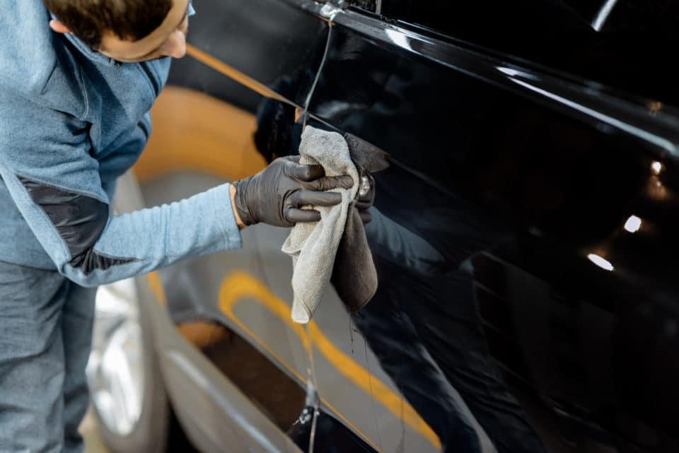 A car detailer carefully washing the exterior of a black car.