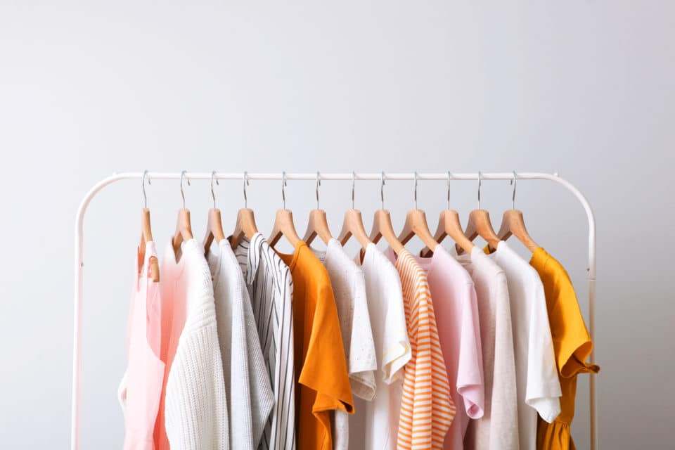 pink, white and orange clothes on a white rack; capsule wardrobe.