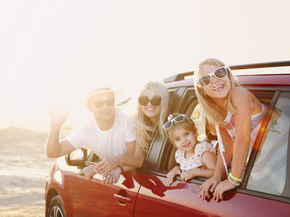 Family smiling at a pitstop during their road trip