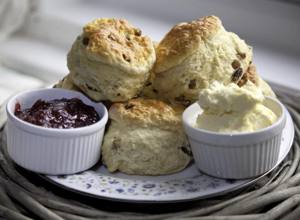 Several scone stacked on a porcelain plate with ramekins filled with raspberry jam and clotted cream.