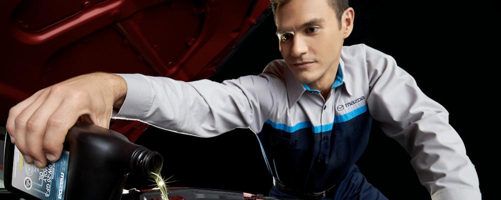 Mazda technician pouring oil into oil filter