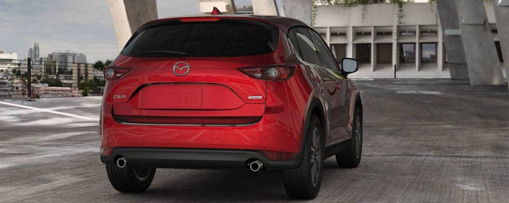 Back view of a red Mazda CX-5 parked on concrete