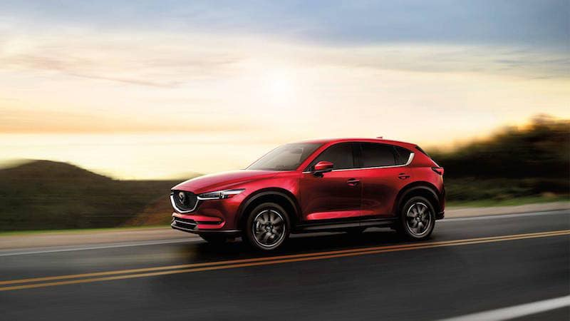 Mazda CX-5 driving on a road in front of the sunset