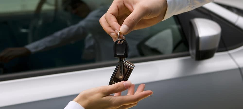 Close up of man handling car keys to woman