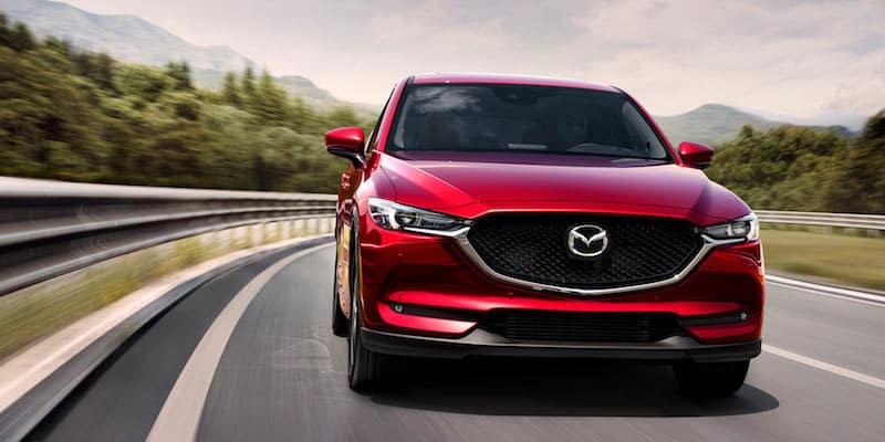 Red front-facing Mazda CX-5 driving down a highway with trees and mountains in the background