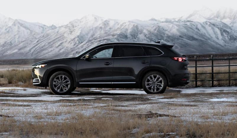 Black Mazda CX-9 parked in front of snow-capped mountain