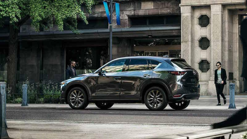 Silver Mazda CX-5 parked in front of a gray brick building