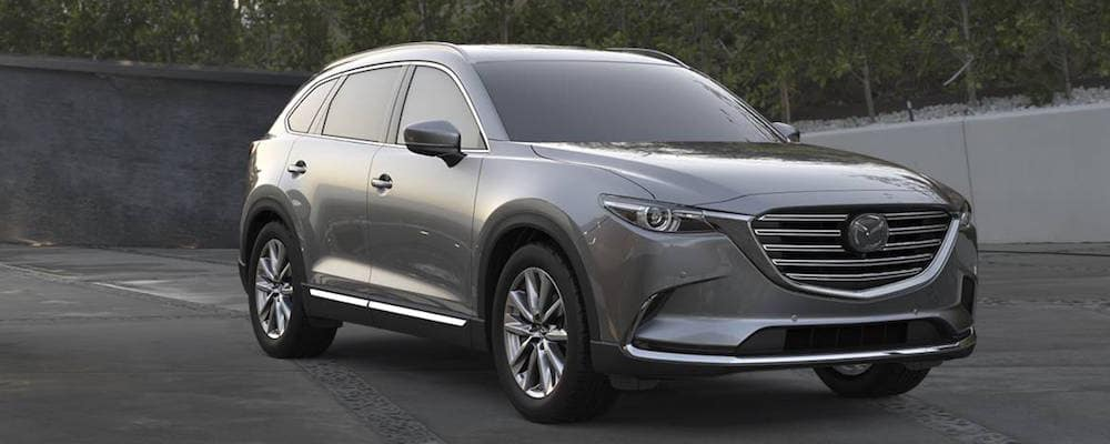 Silver Mazda CX-9 parked in front of a concrete wall with trees behind it