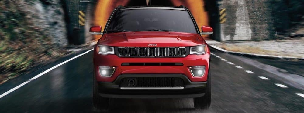 2019 red Jeep Compass driving out of a tunnel