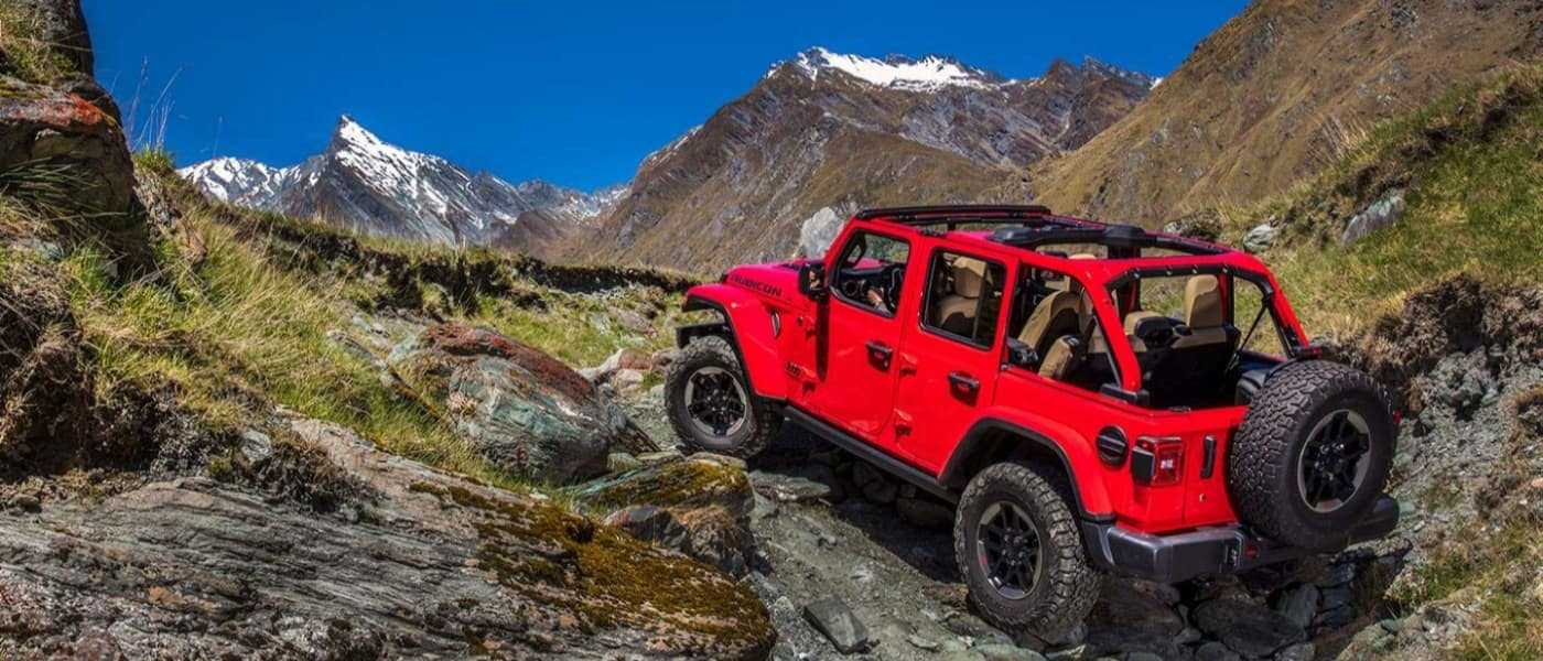 2020 Red Jeep Wrangler Driving up a Mountain