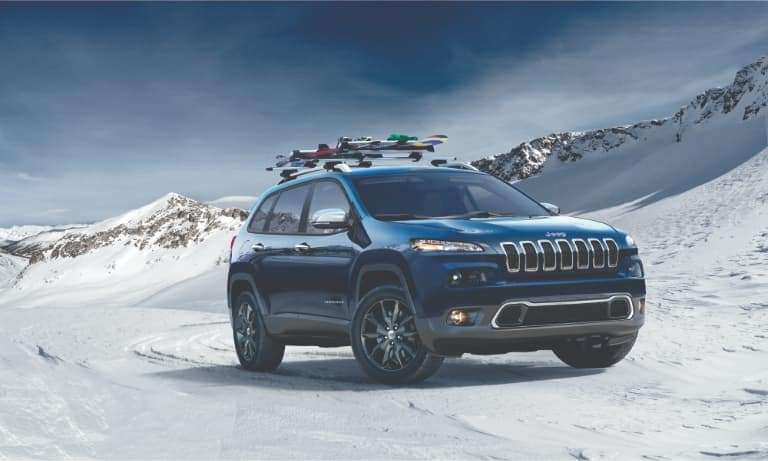 Jeep Cherokee Driving in Snow with a Roof Rack of Skis