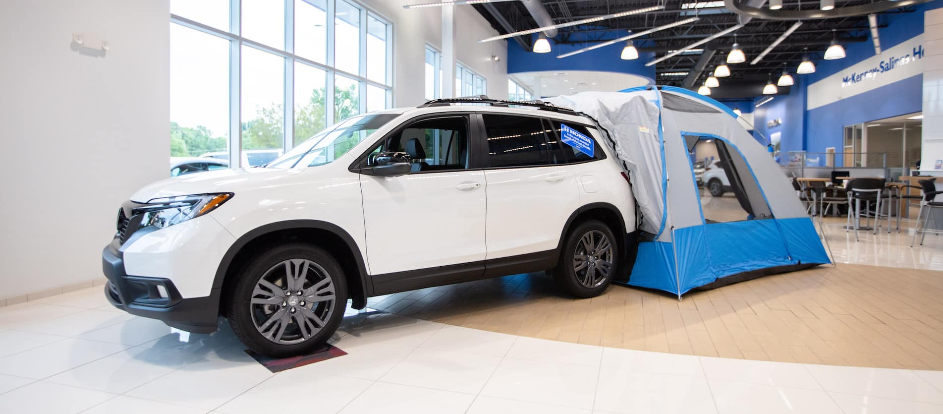 Honda SUV with tent off rear of vehicle inside showroom