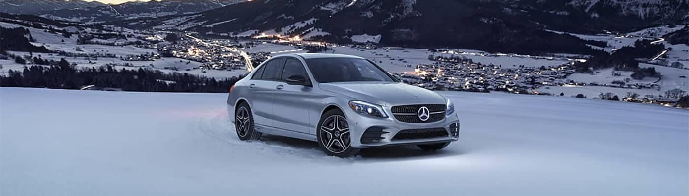 Mercedes-Benz C-Class Parked in Snow with Town Behind