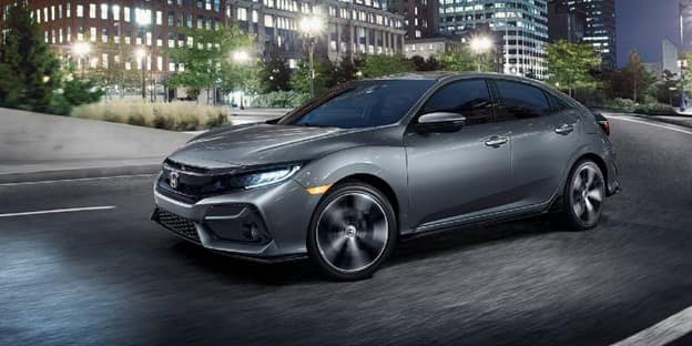 gray 2021 Honda Civic Hatchback with LED lights and a black grille driving down a city street with brick buildings in the background