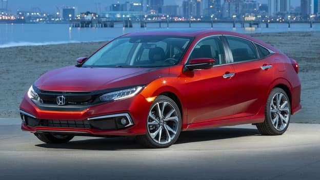 red 2021 Honda Civic sedan parked by a beach at dusk with a city in the background
