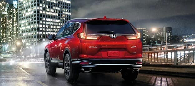 red 2021 Honda CR-V with LED tail lights driving at night on a highway at night in the rain