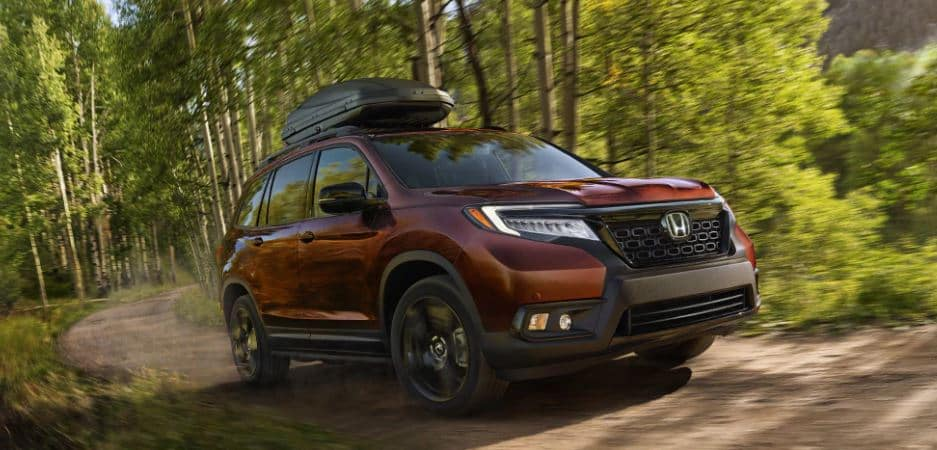 blue 2021 Honda Passport SUV with a black grille and rims driving past a brick building