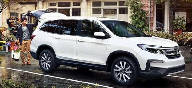 white 2021 Honda Pilot three-row SUV driving on a paved road past trees on either side with leaves changing color