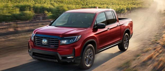 red 2021 Honda Ridgeline pickup truck with a black grille and mirror caps driving down a dirt road