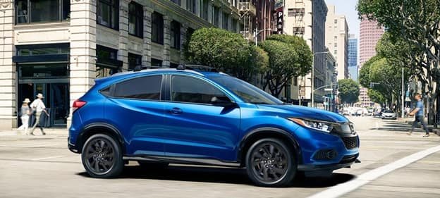 blue 2021 Honda HR-V subcompact SUV driving down a city street on a sunny day