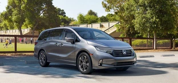 gray 2021 Honda Odyssey minivan with a black grille parked near a brown fence near a soccer field