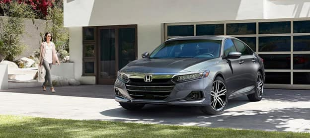 woman walking towards a new gray 2021 Honda Accord full-size sedan parked in front of a white building