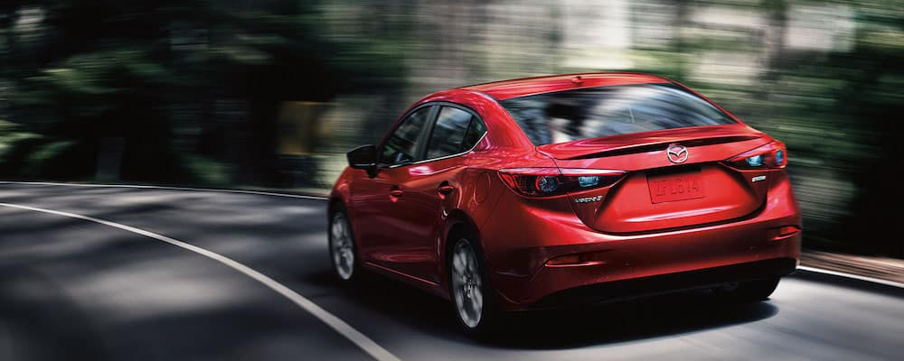 Rear of Red Mazda3 going left on curve with blurry woods background