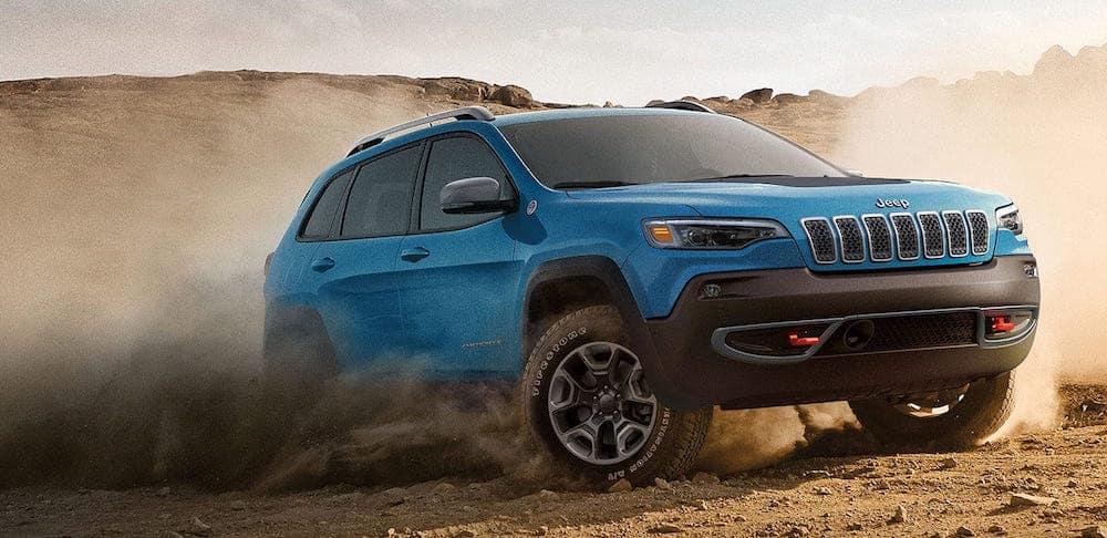 Blue Jeep Cherokee driving through a sandy terrain