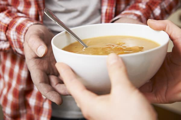 Close up of someone handing a bowl of soup to someone else