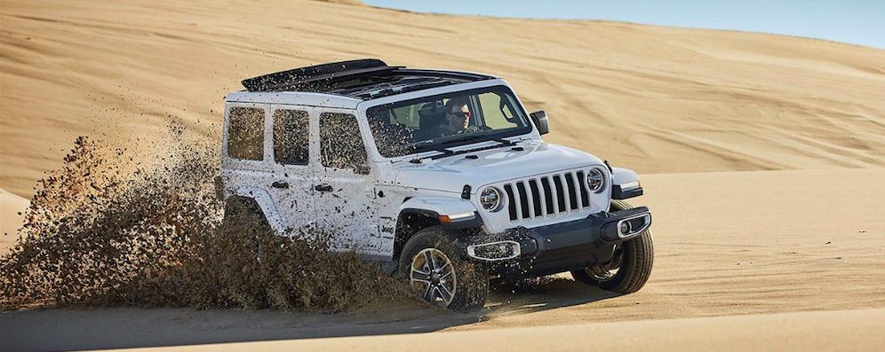 White Jeep Wrangler driving through sand