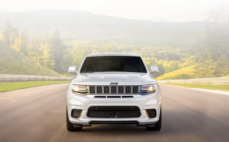 White Jeep Grand Cherokee driving head on on a highway