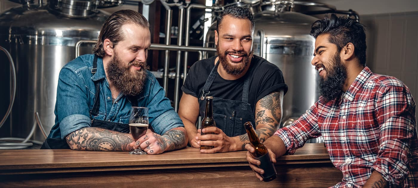 Men laughing and drinking at a brewery