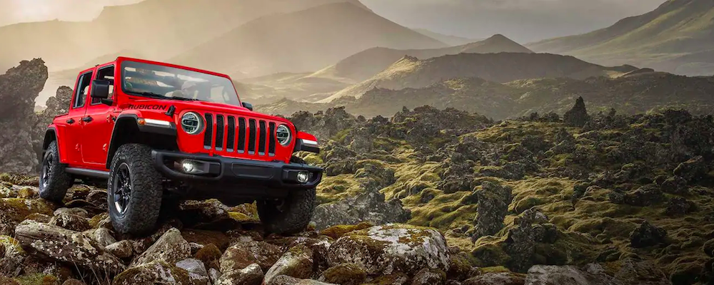 Red Jeep Wrangler parked on a hill